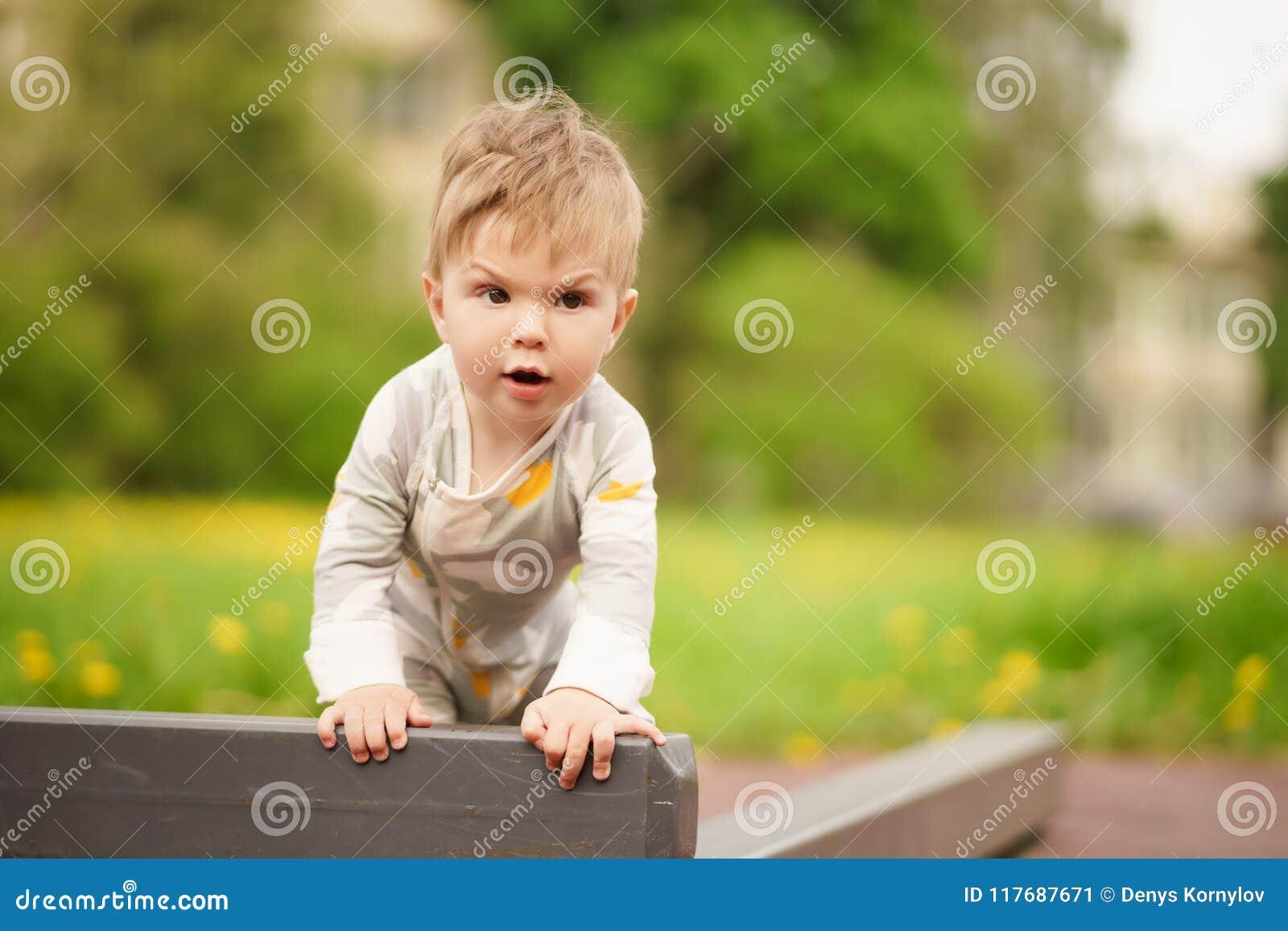 Juego Adorable Del Bebe En El Patio Al Aire Libre Con La Cara Seria