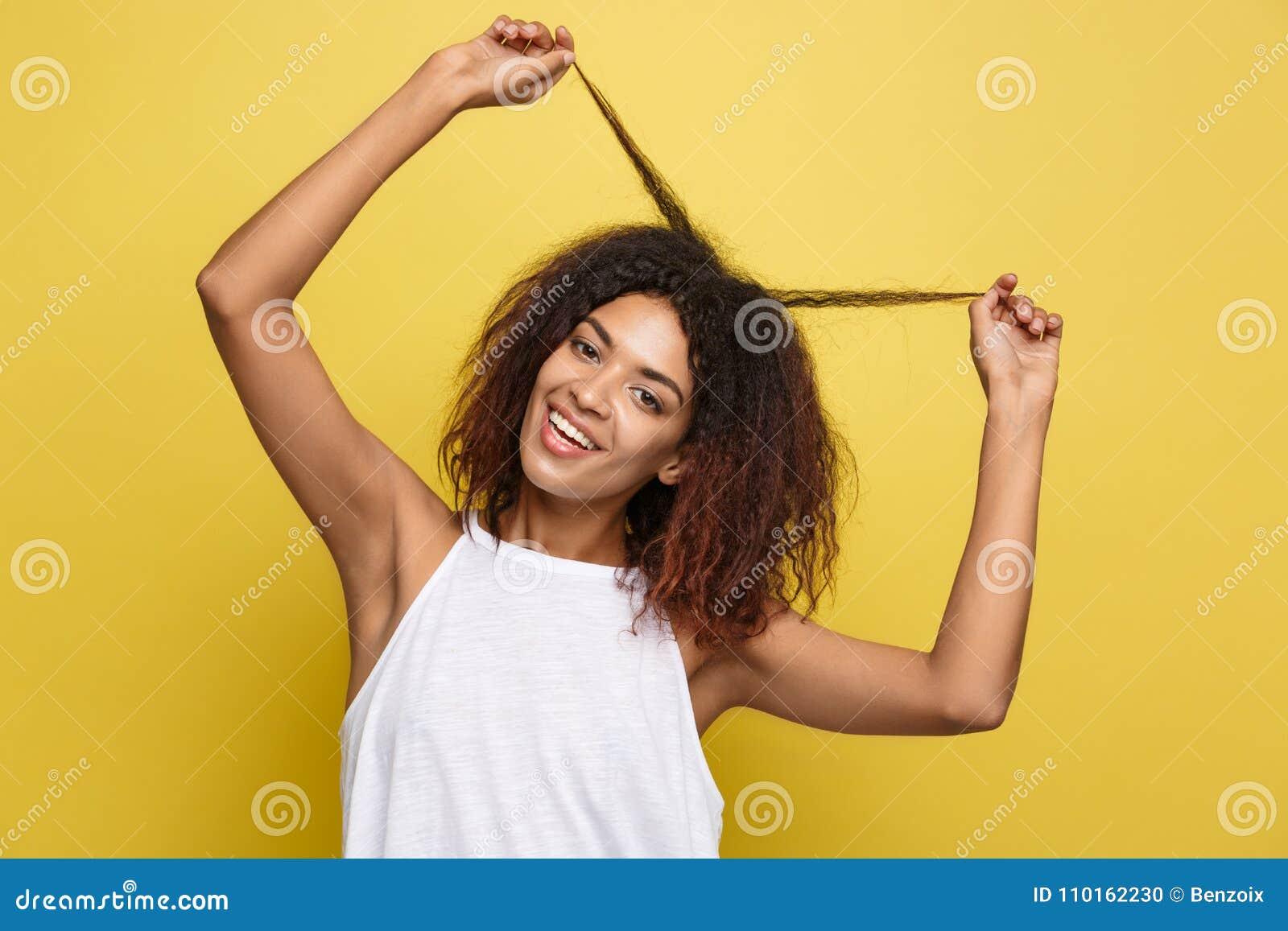 Juego afroamericano atractivo hermoso de la fijación de la mujer con su pelo afro rizado Fondo amarillo del estudio Copie el espa