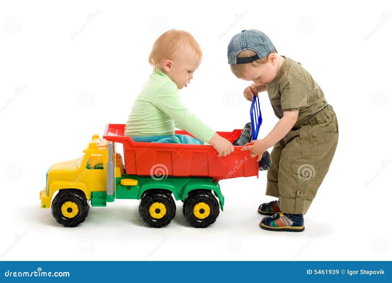 Juego de dos niños pequeños con el carro del juguete