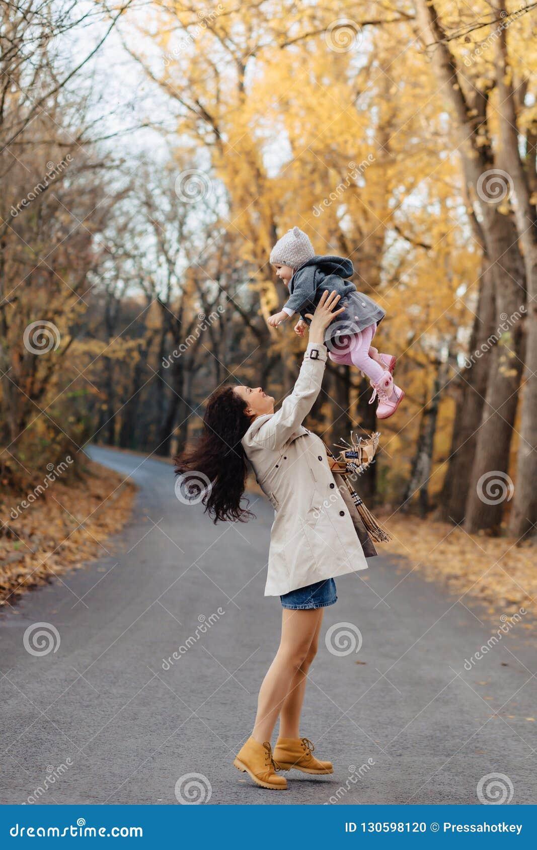 Juego de la mamá de la mujer joven con poca hija en el camino del parque del otoño