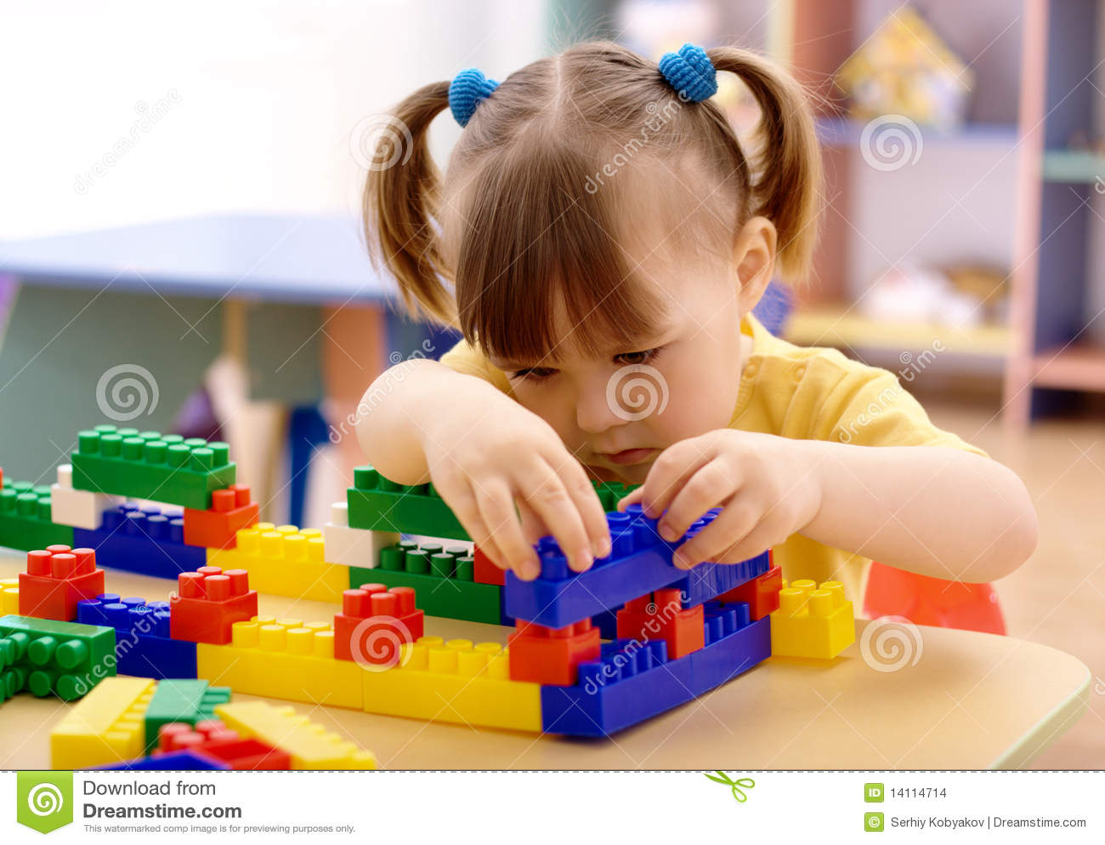 Juego de la niña con los ladrillos del edificio en pre-entrenamiento