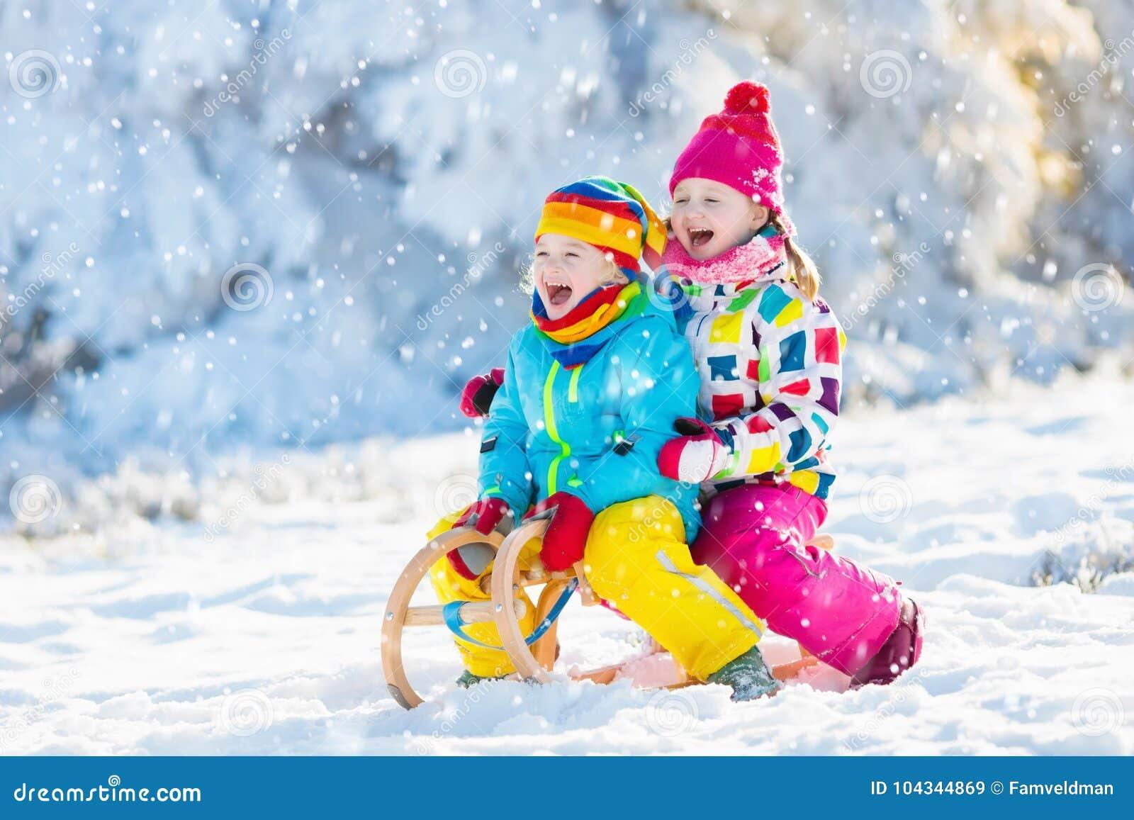 Juego de los niños en nieve Paseo del trineo del invierno para los niños