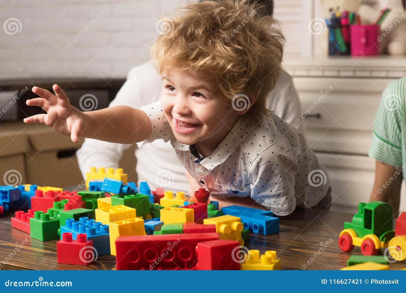 Juego de niños con los ladrillos de la construcción del juguete Concepto de los juegos de la familia