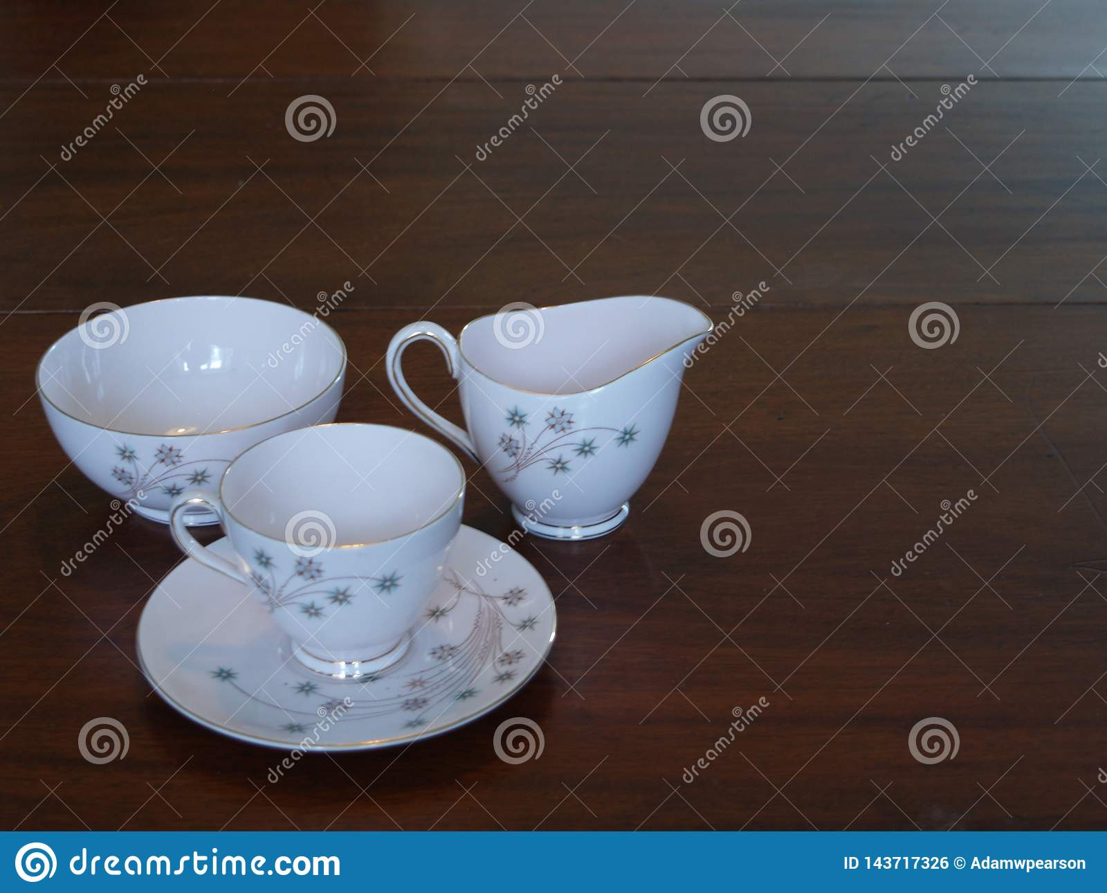 Juego de té del vintage en la mesa de comedor de caoba
