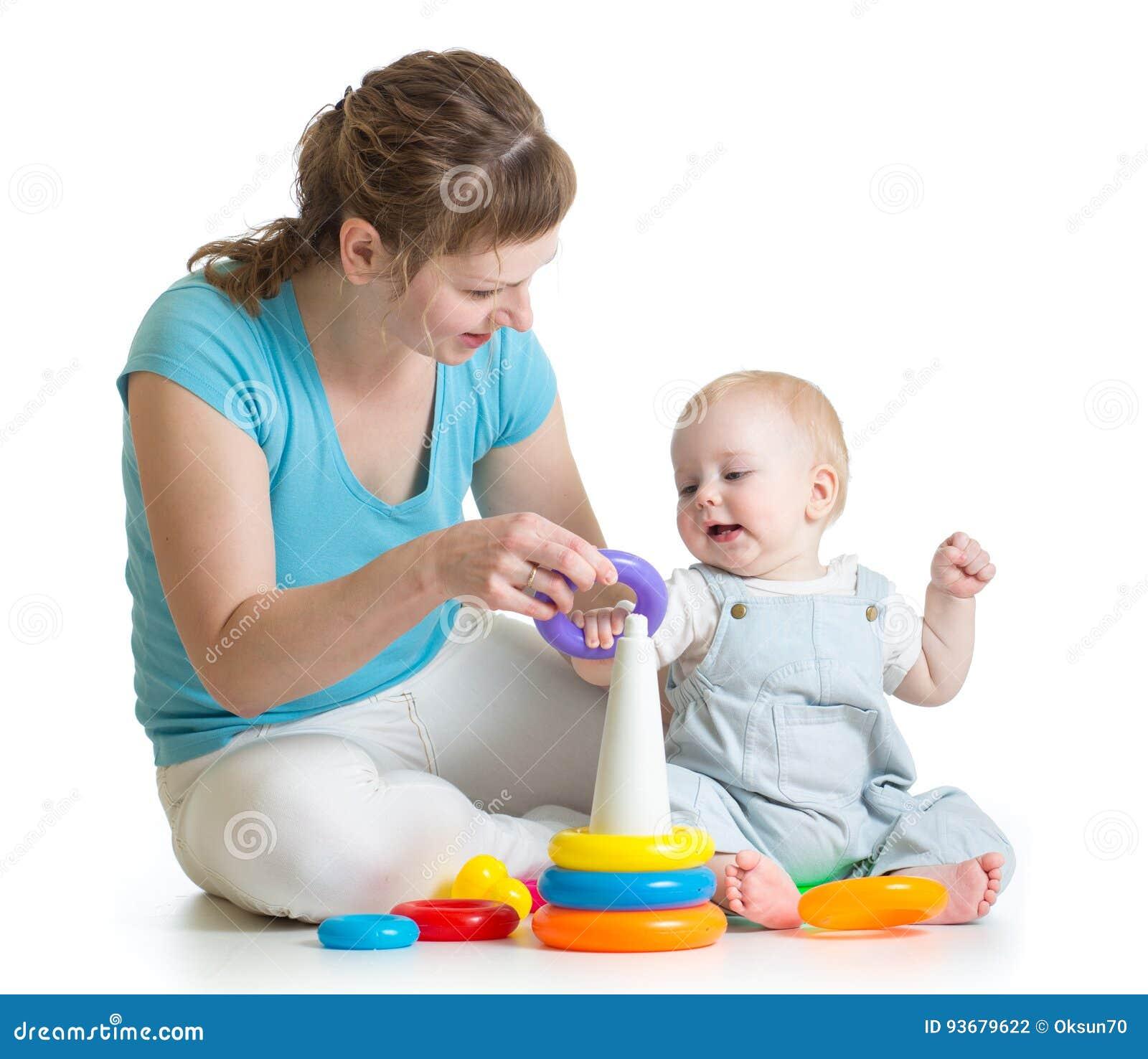 Juego del niño y de la mamá con los juguetes del bloque