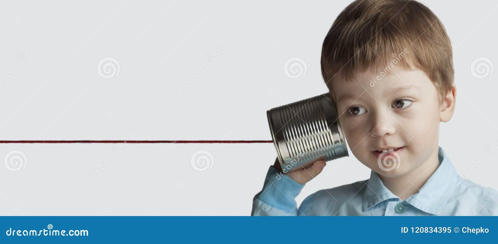 Juego feliz del muchacho en el teléfono de la lata
