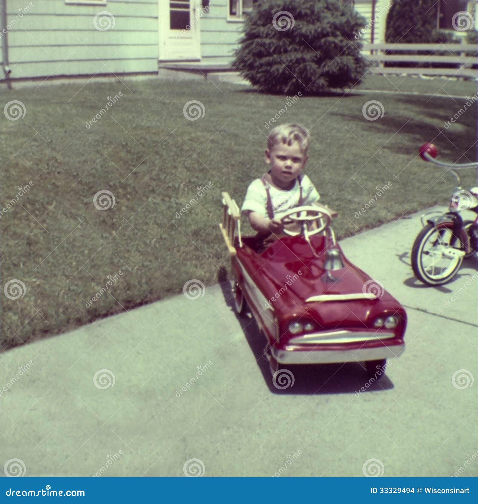 Juego joven del muchacho de la foto retra del vintage en coche del pedal