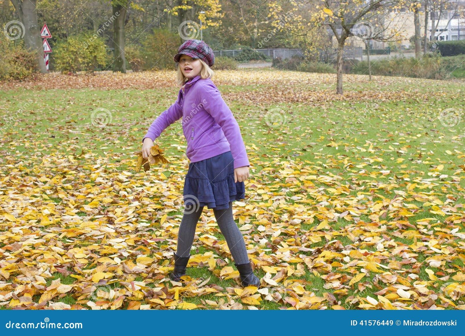 Juegos de la niña con las hojas de otoño