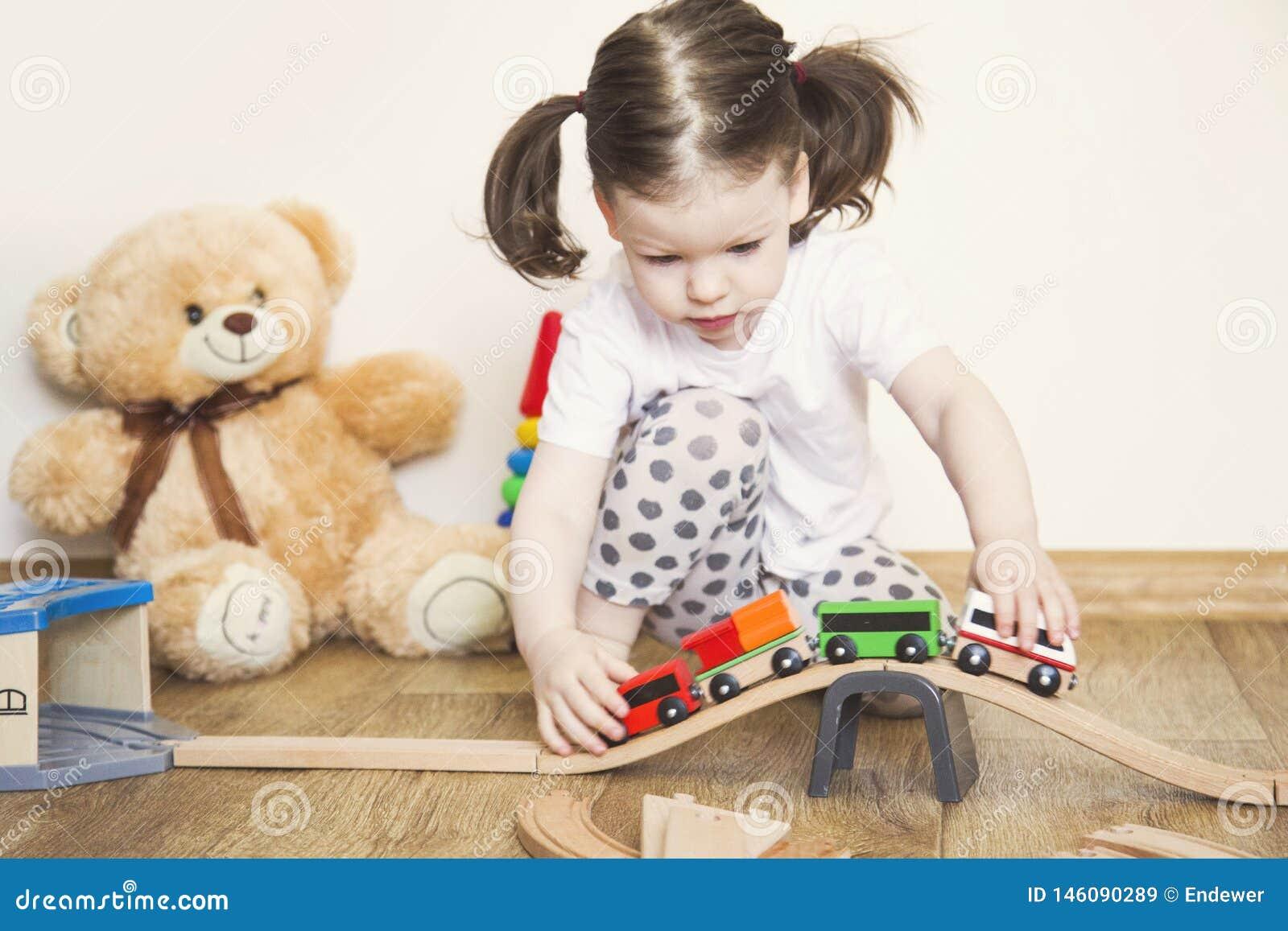 Juegos de la ni?a con los juguetes, el ferrocarril de madera y el tren