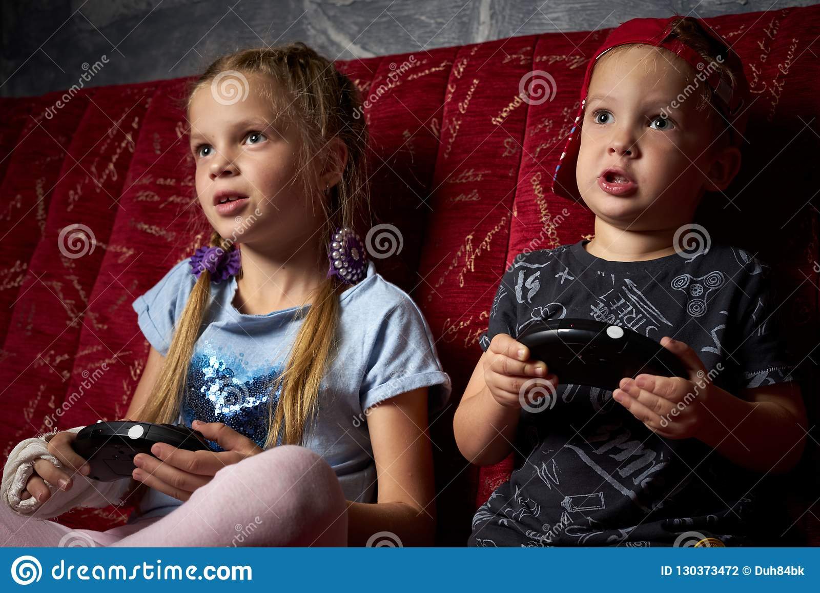 Juegos de ordenador: un muchacho y una muchacha juegan una videoconsola en la oscuridad y llevan a cabo gamepads en sus manos
