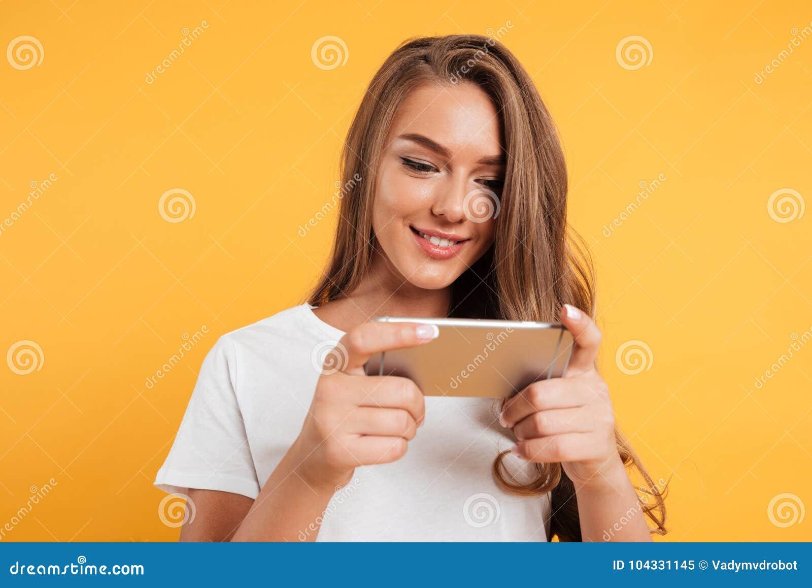 Juegos hermosos lindos felices del juego de la mujer joven por el teléfono móvil
