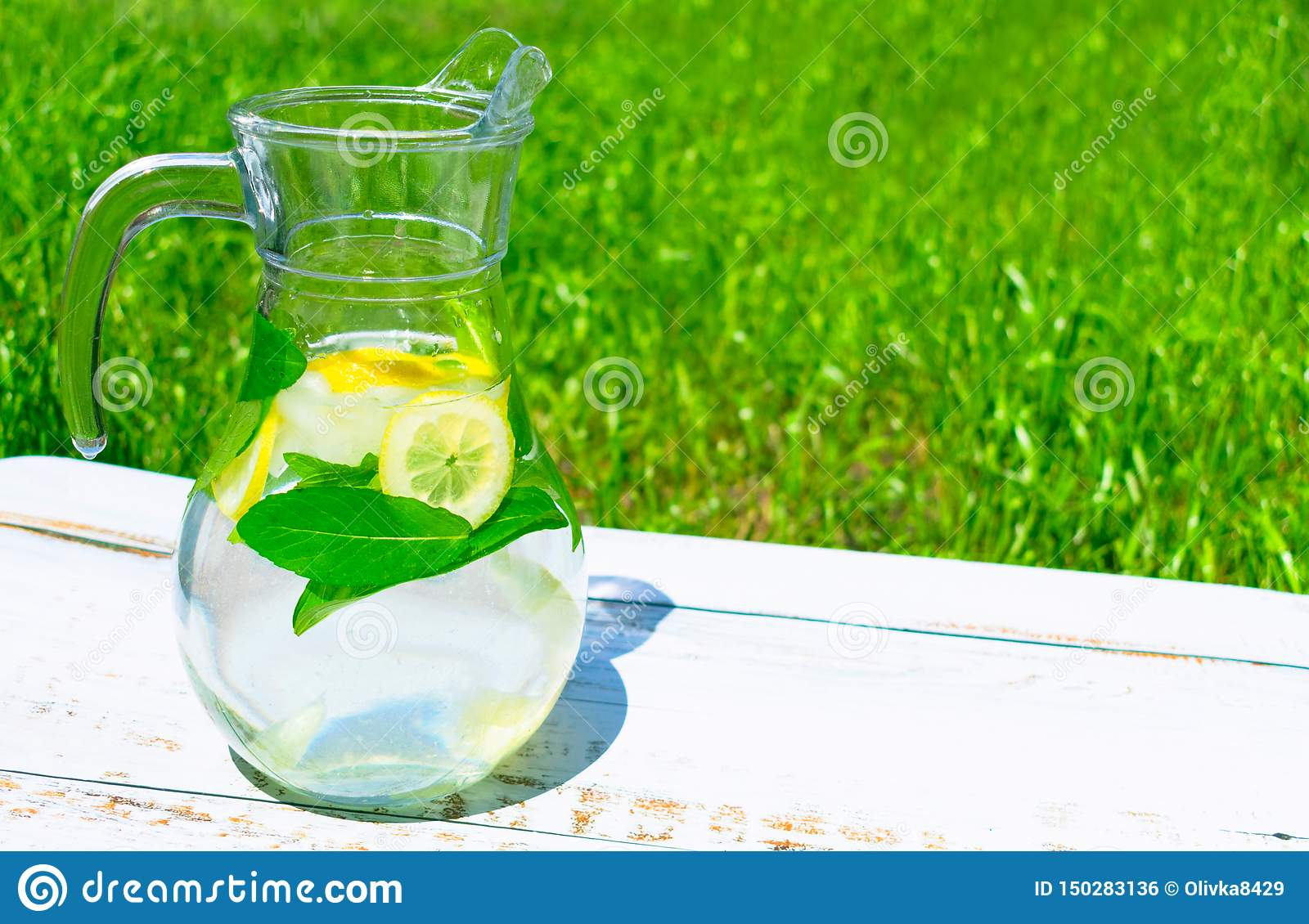 Jug with lemonade from lemon and mats with ice on a background of green grass. The concept of soft drinks. Close-up ..