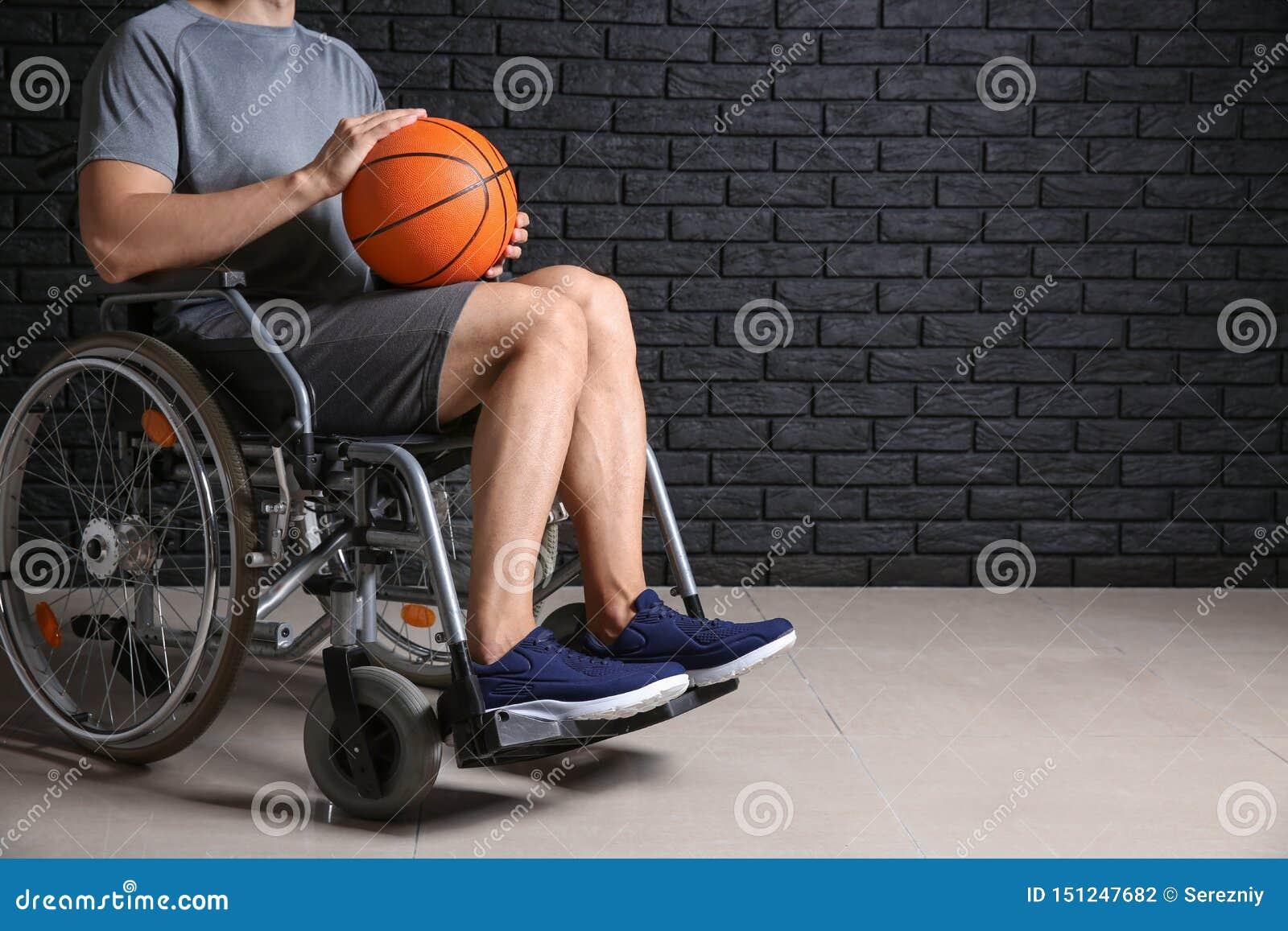 Jugador de básquet joven que se sienta en silla de ruedas contra la pared de ladrillo oscura