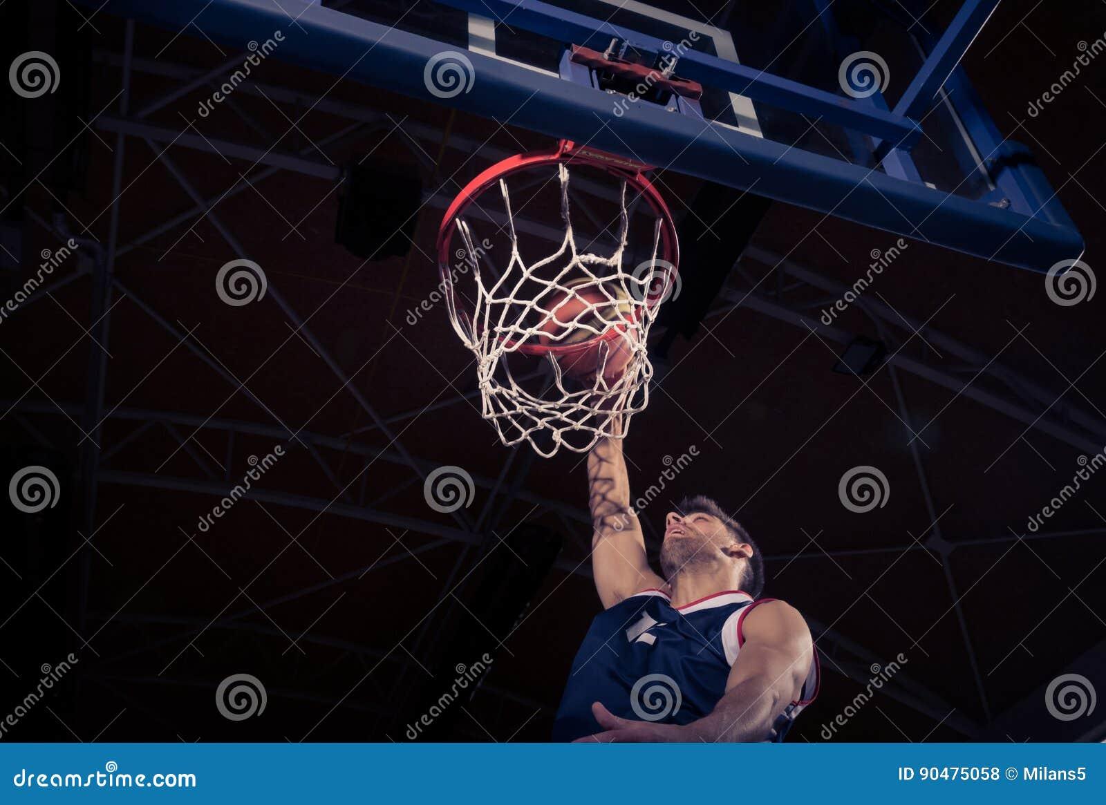 Jugador de básquet, opinión de ángulo bajo, clavada