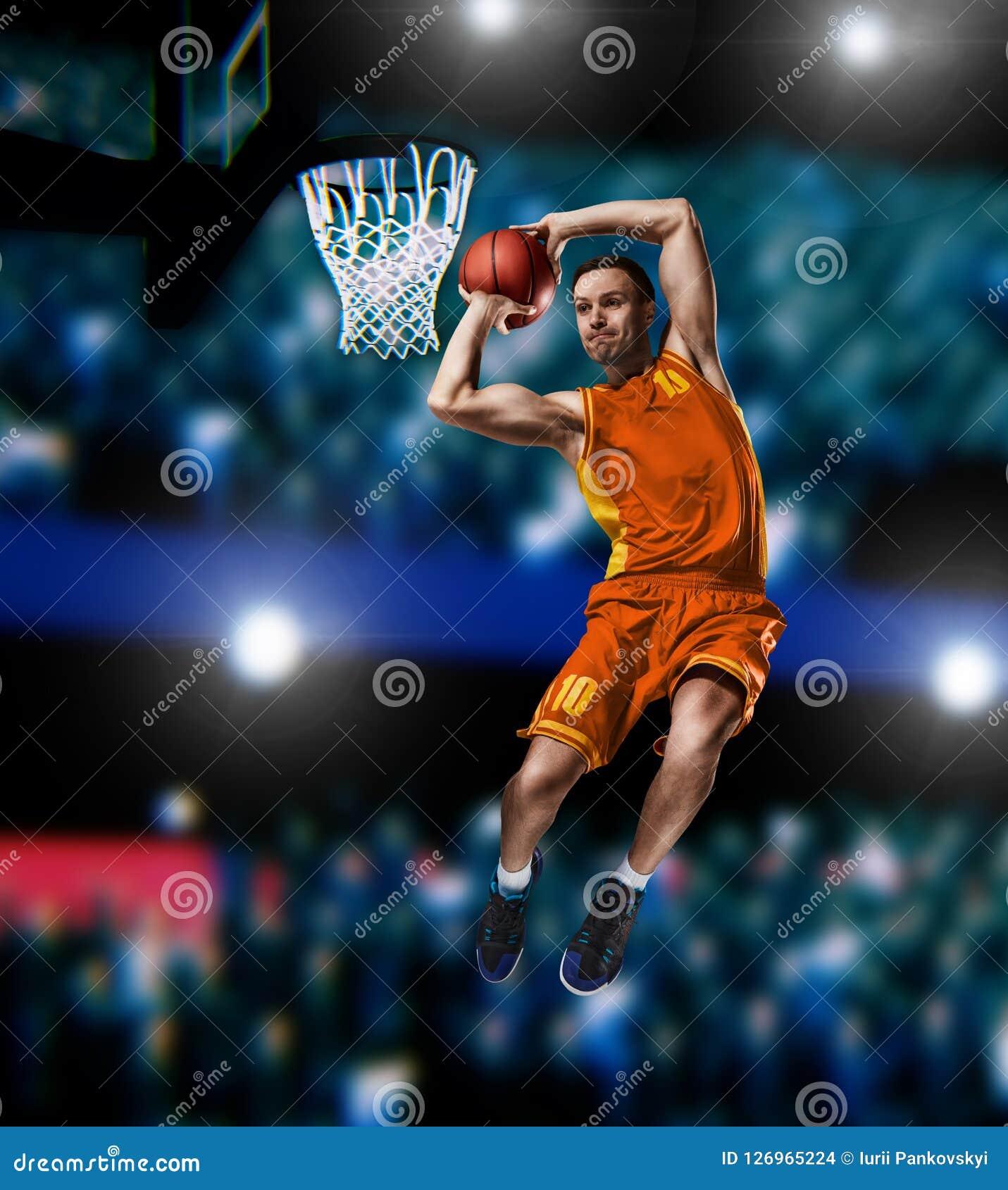 Jugador de básquet que hace clavada en arena del baloncesto