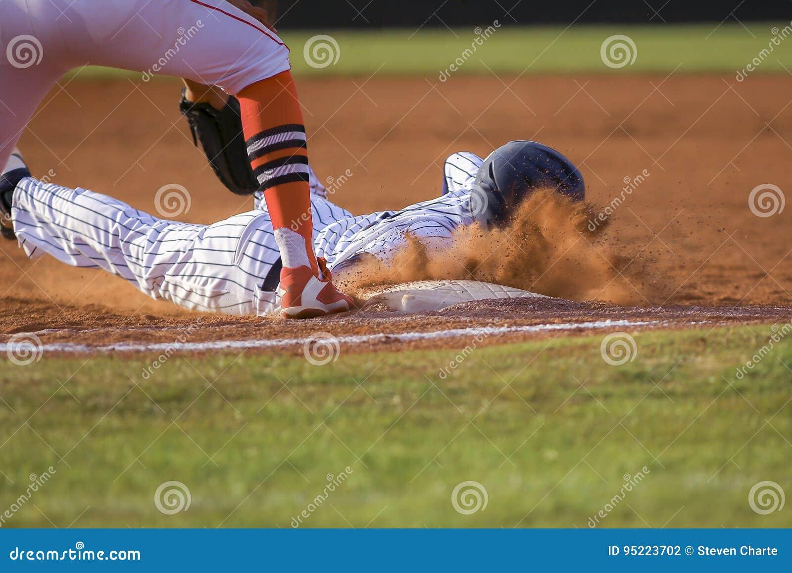 Jugador de béisbol que desliza la primera base
