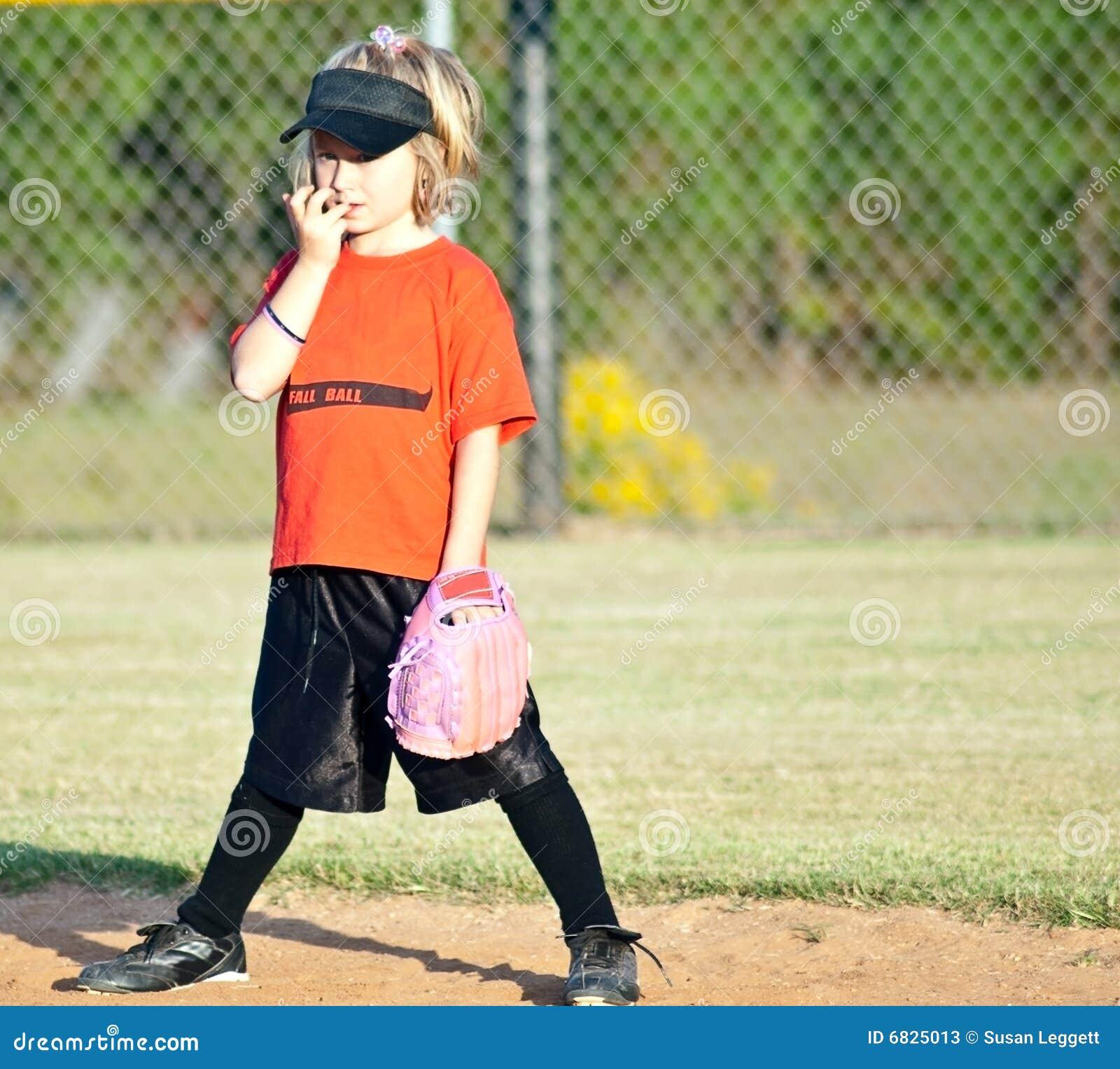 Jugador de beísbol con pelota blanda/muchacha jovenes