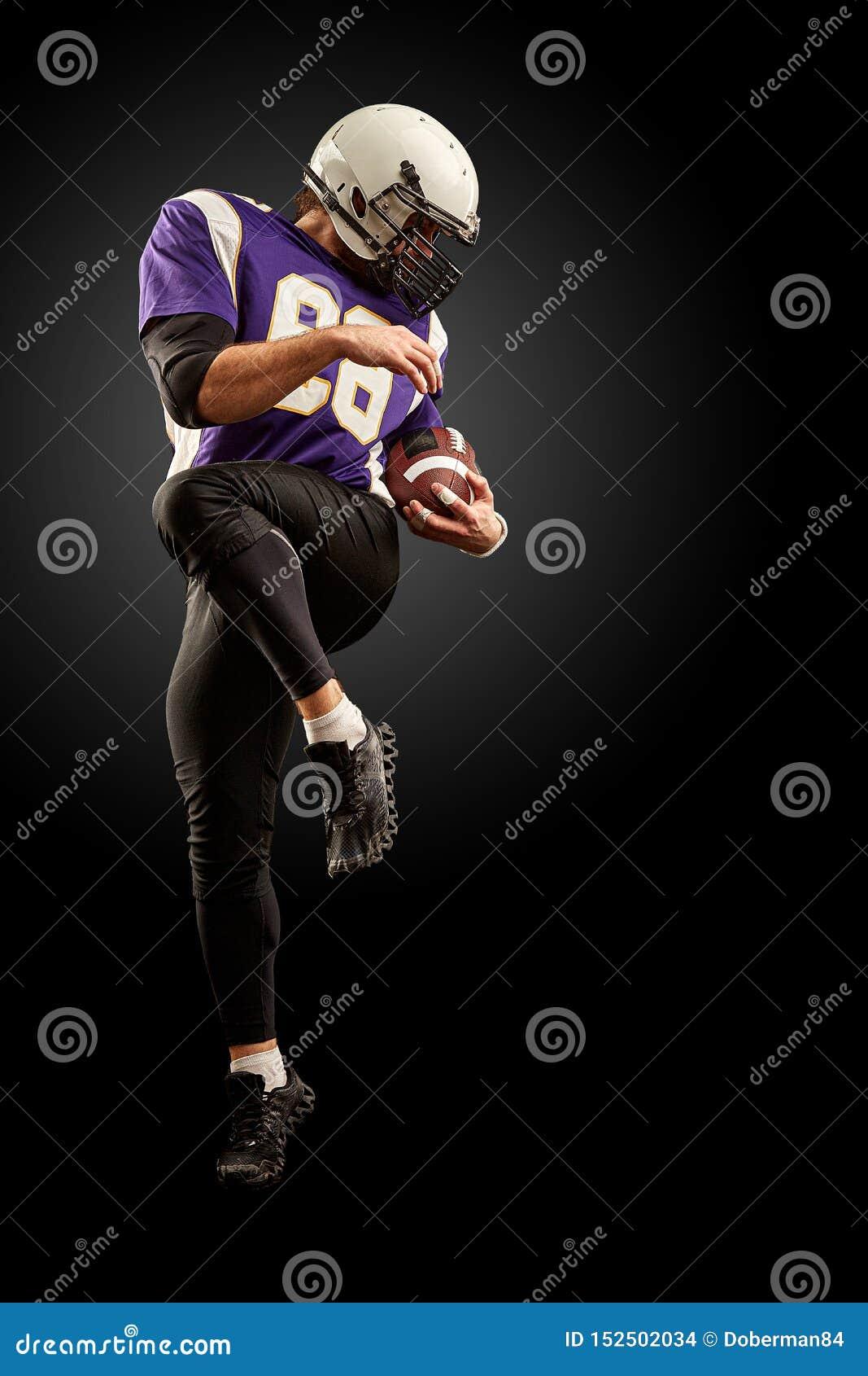 Jugador de fútbol americano que celebra una bola mientras que salta lejos de una huelga fondo negro, espacio de la copia Violeta