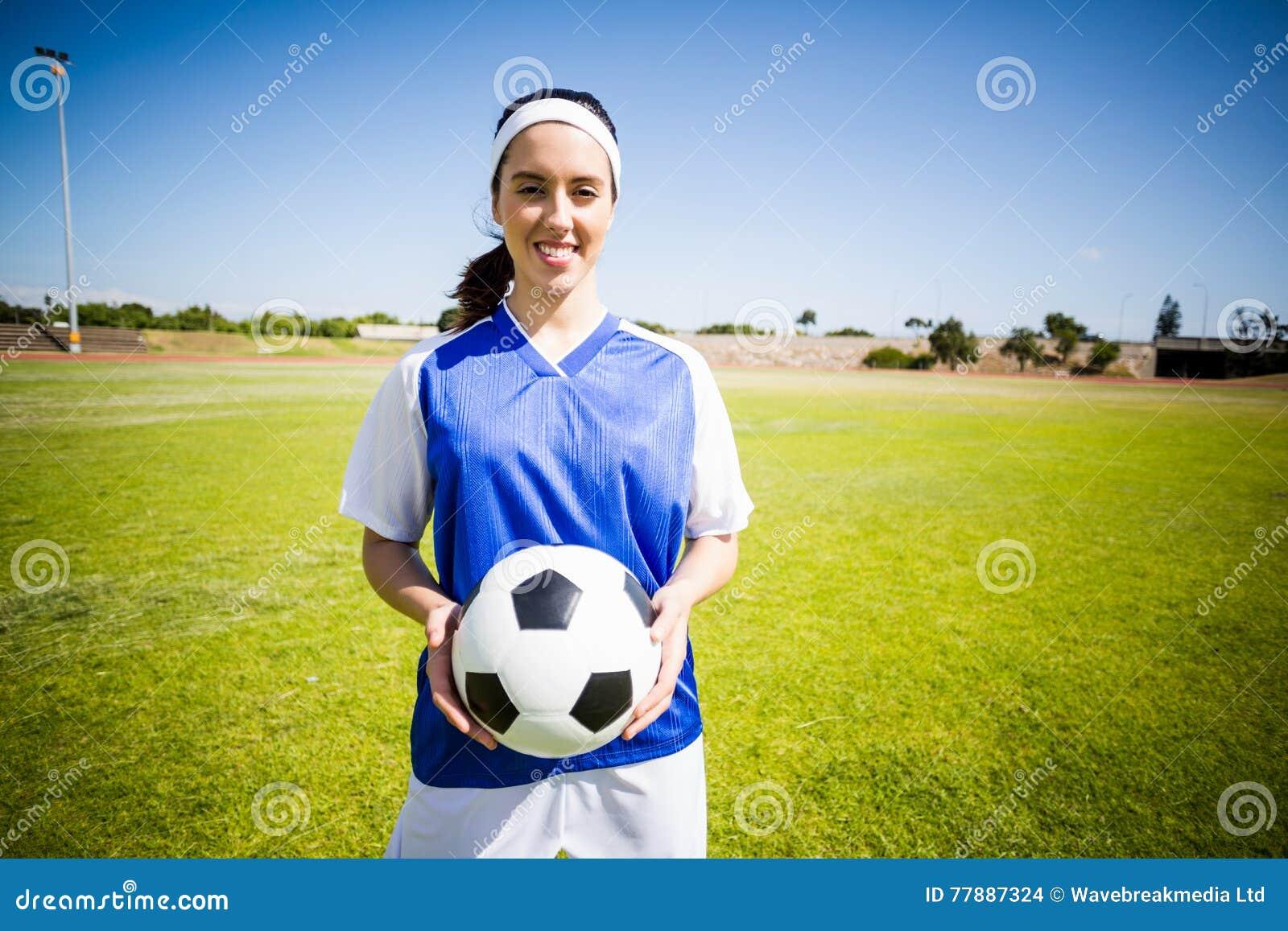 Jugador De Fútbol Feliz Que Se Coloca Con Una Bola Foto de archivo