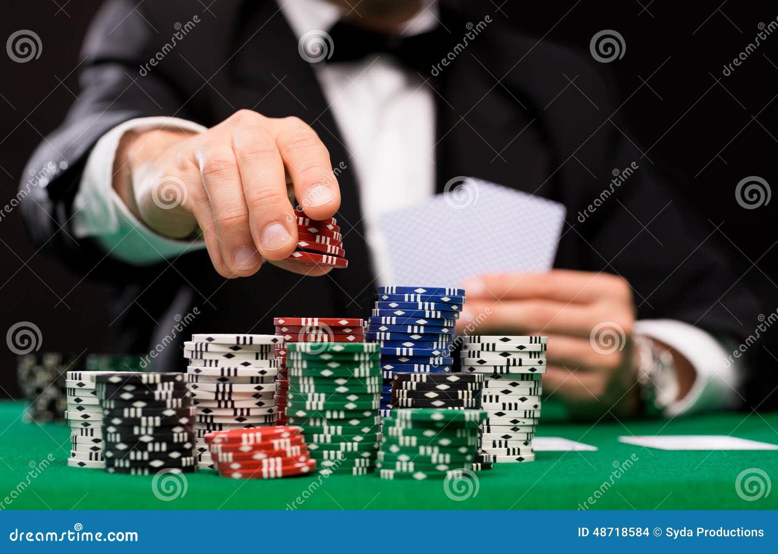 Jugador de póker con las tarjetas y los microprocesadores en el casino
