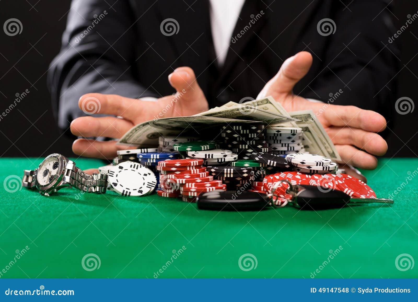 Jugador de póker con los microprocesadores y dinero en la tabla del casino