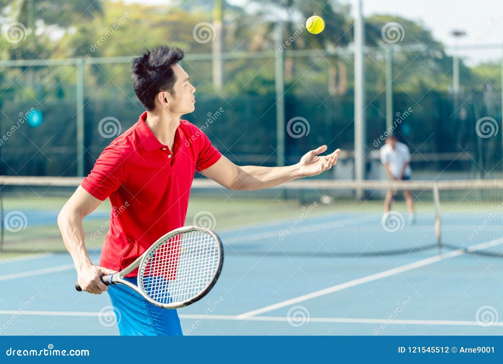 Jugador de tenis chino listo para golpear la bola mientras que sirve en un partido del tenis
