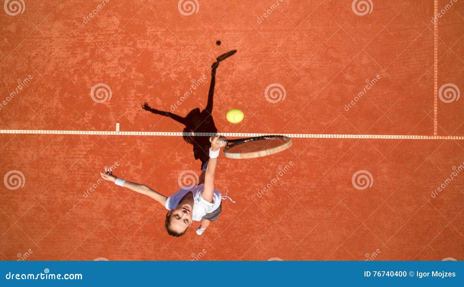 Jugador de tenis que golpea la bola en terreno del tenis