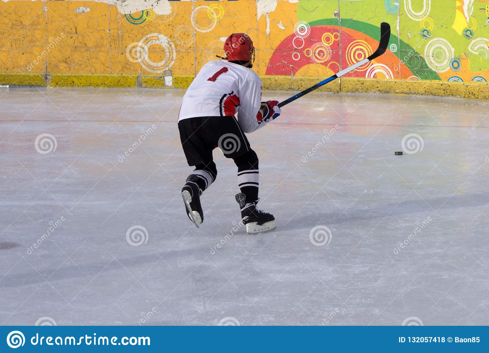 Jugador del hockey sobre hielo en la acción que golpea con el pie con el palillo