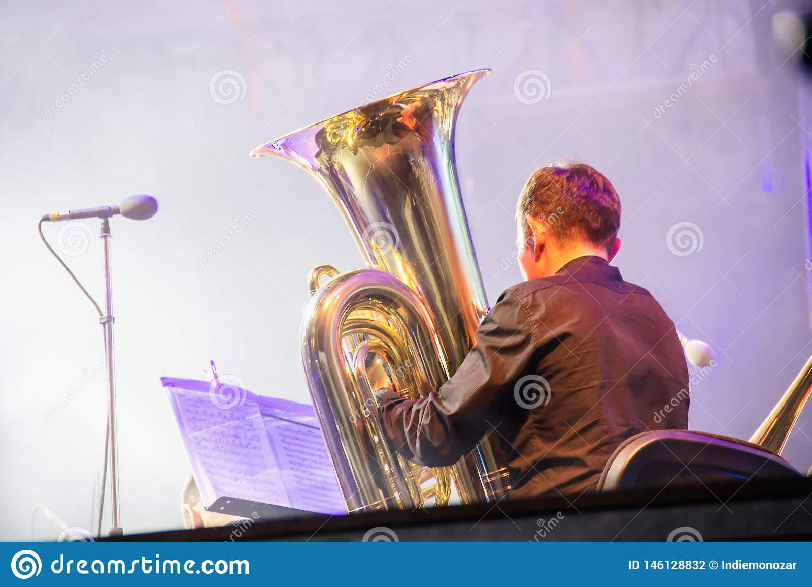 Jugador en una orquesta en la etapa, juegos de la tuba en el tubo de cobre amarillo grande, detrás del lanzamiento de las escenas