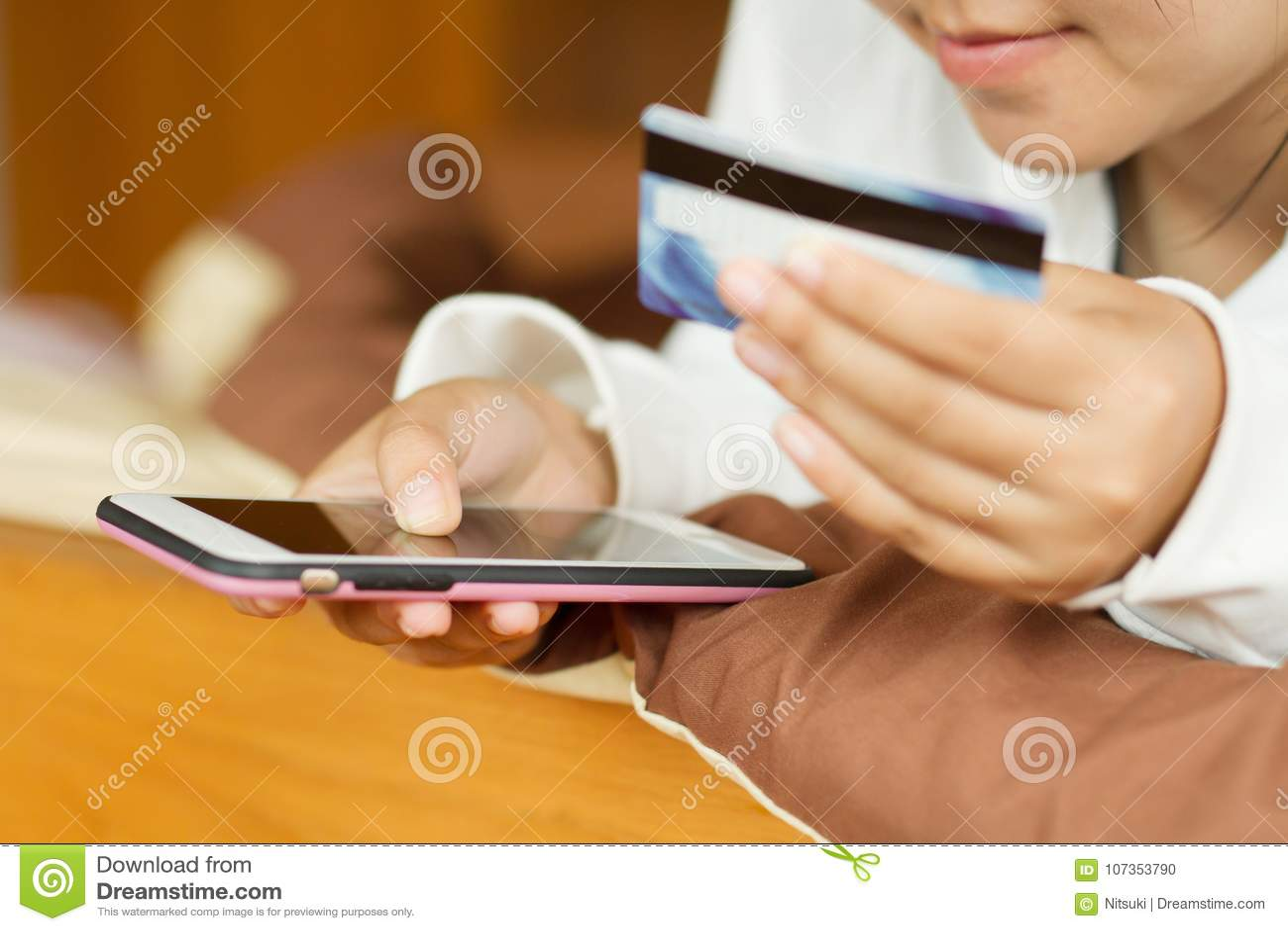 Jugend von der Frau, die intelligentes Telefon mit Kreditkarte beim auf Internet zu Hause kaufen hält