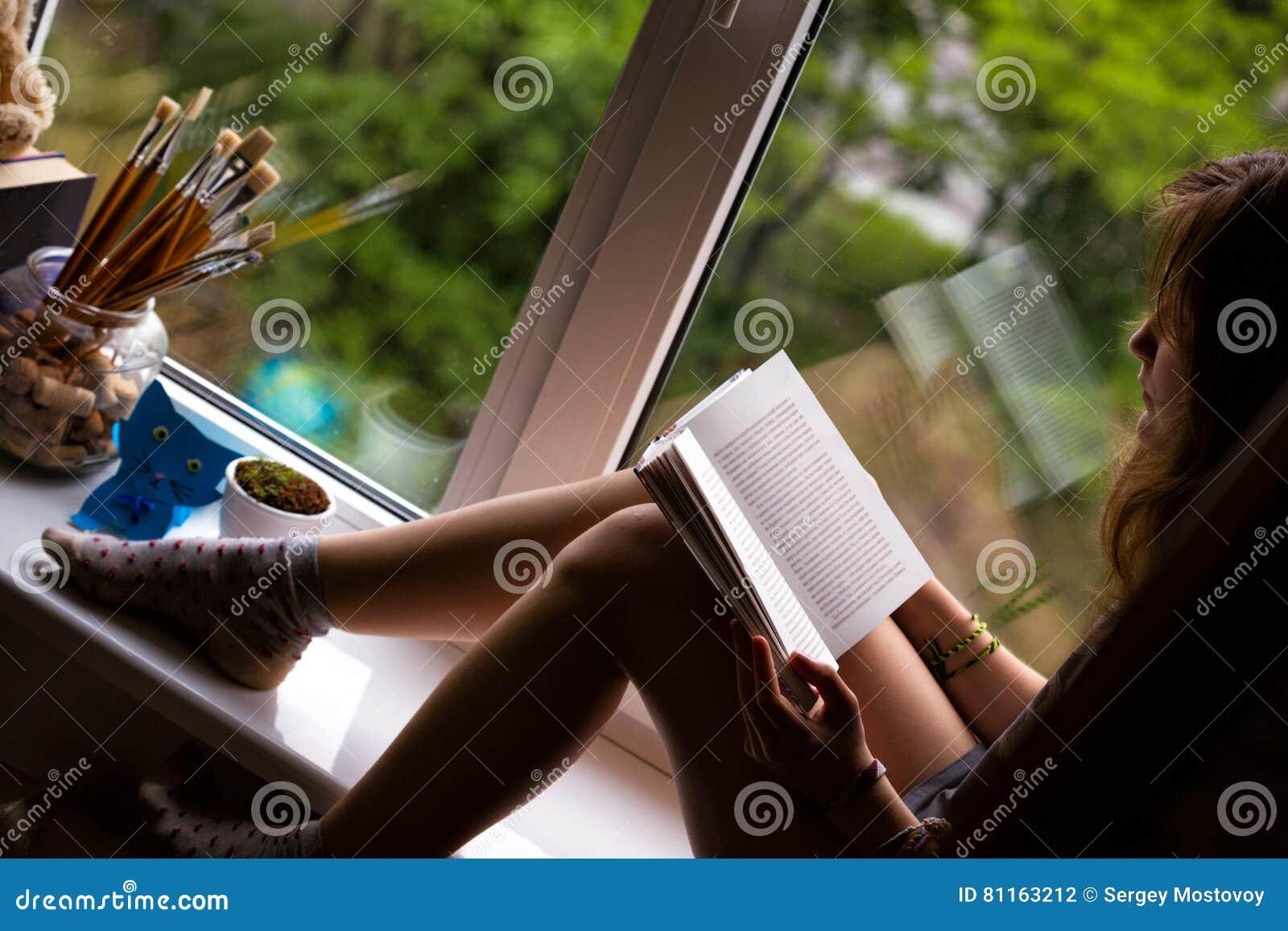 Jugendlich Mädchen, das auf einem Fensterbrett sitzt