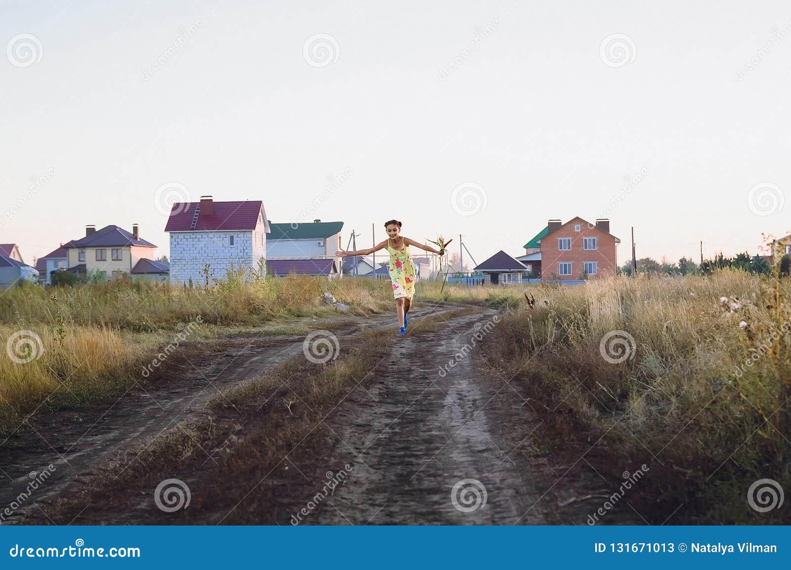 Jugendlich Mädchen in einem gelben Kleid, das auf dem Feld, Sommer läuft
