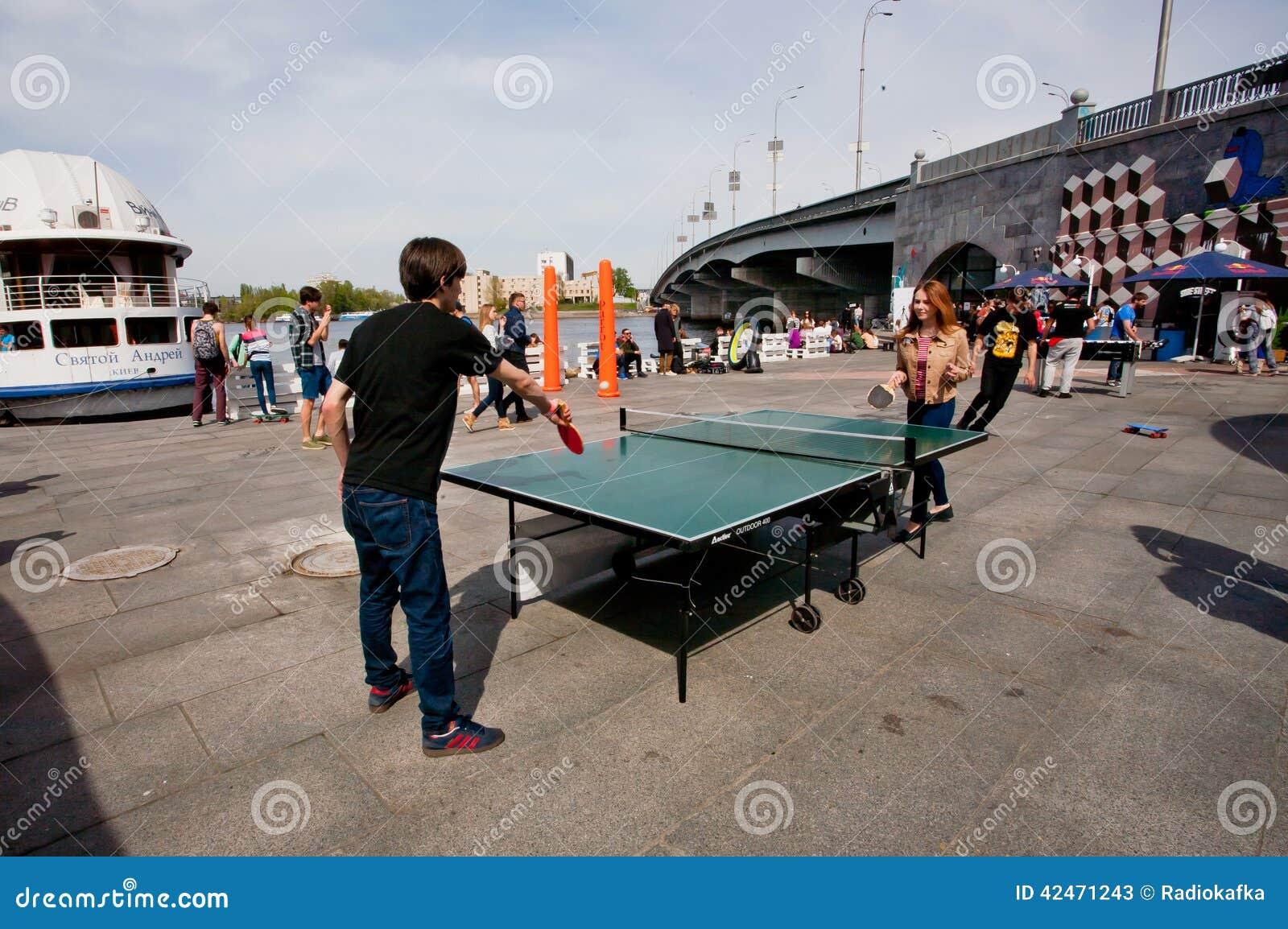 Jugendlich Mädchen und Junge spielen Klingeln pong im Freien
