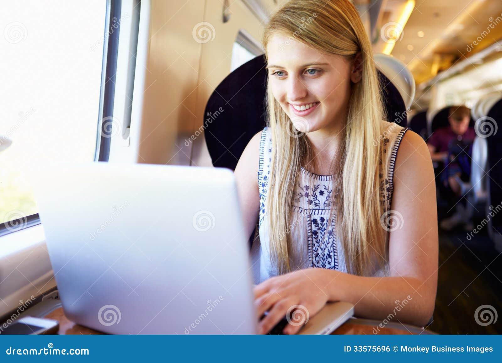 Jugendliche, die Laptop auf Zug-Reise verwendet