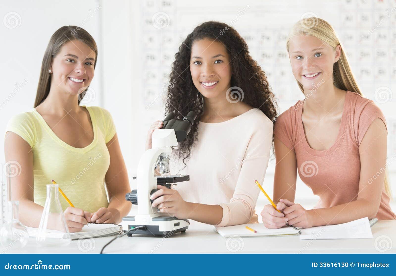 Jugendlichen mit mikroskop am schreibtisch im chemieunterricht