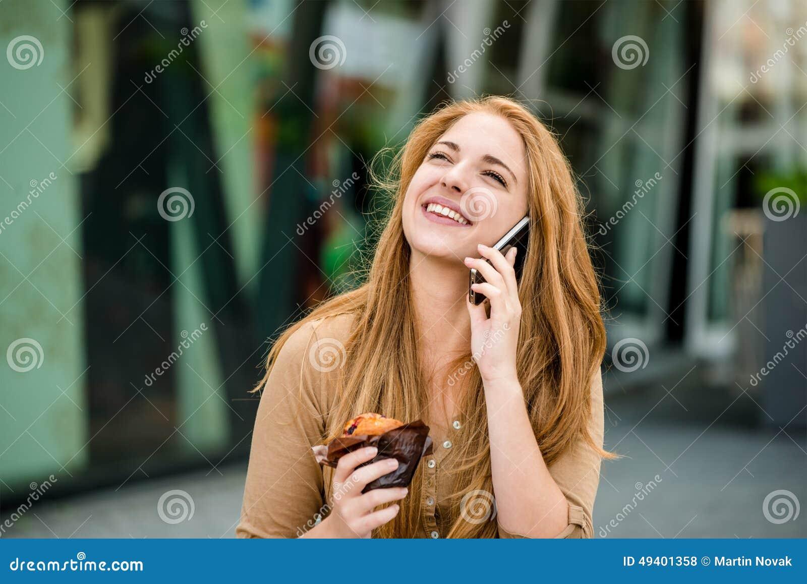 Download Jugendlicher, Der Das Muffin Schaut Im Telefon Isst Stockfoto - Bild von authentisch, draußen: 49401358