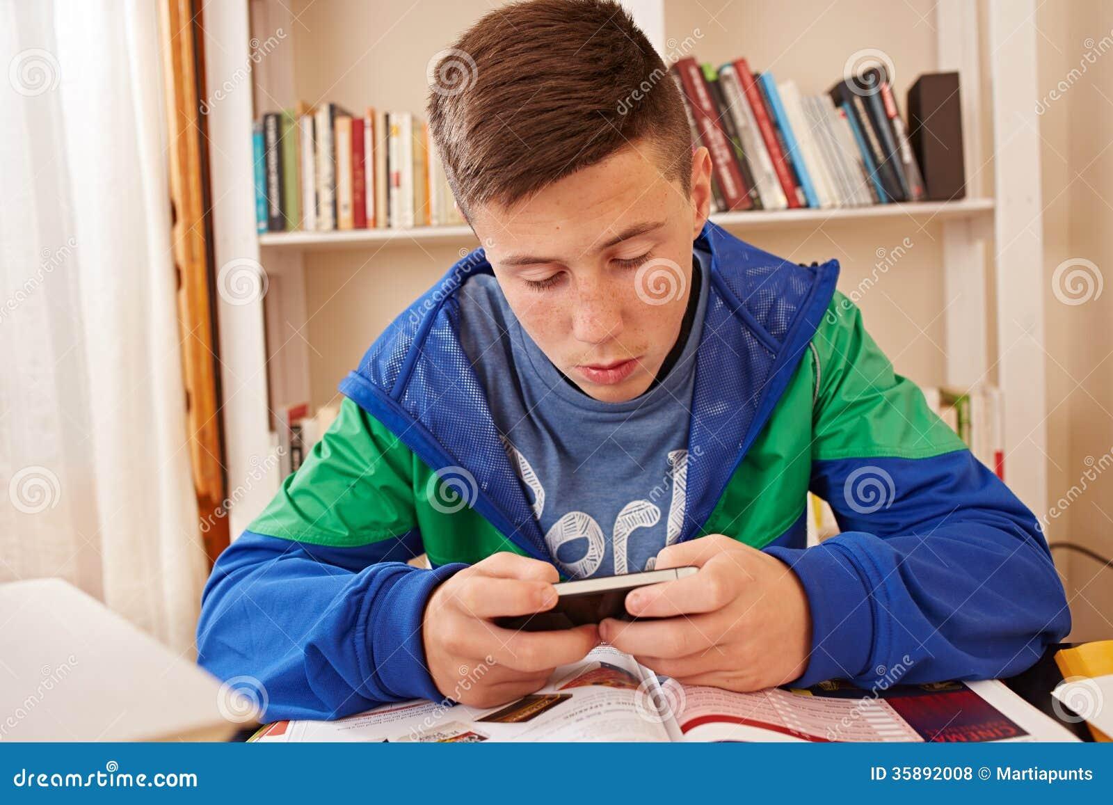 Jugendlicher, der mit Smartphone beim Studieren simst