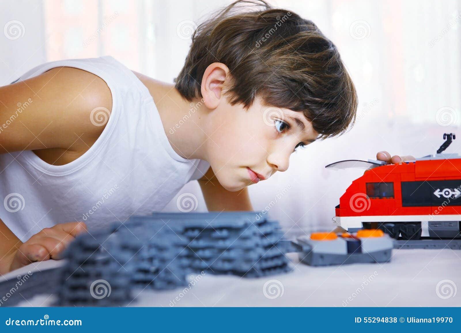 Jugendliches hübsches Jungenspiel mit meccano Spielzeugzug und Eisenbahn sta