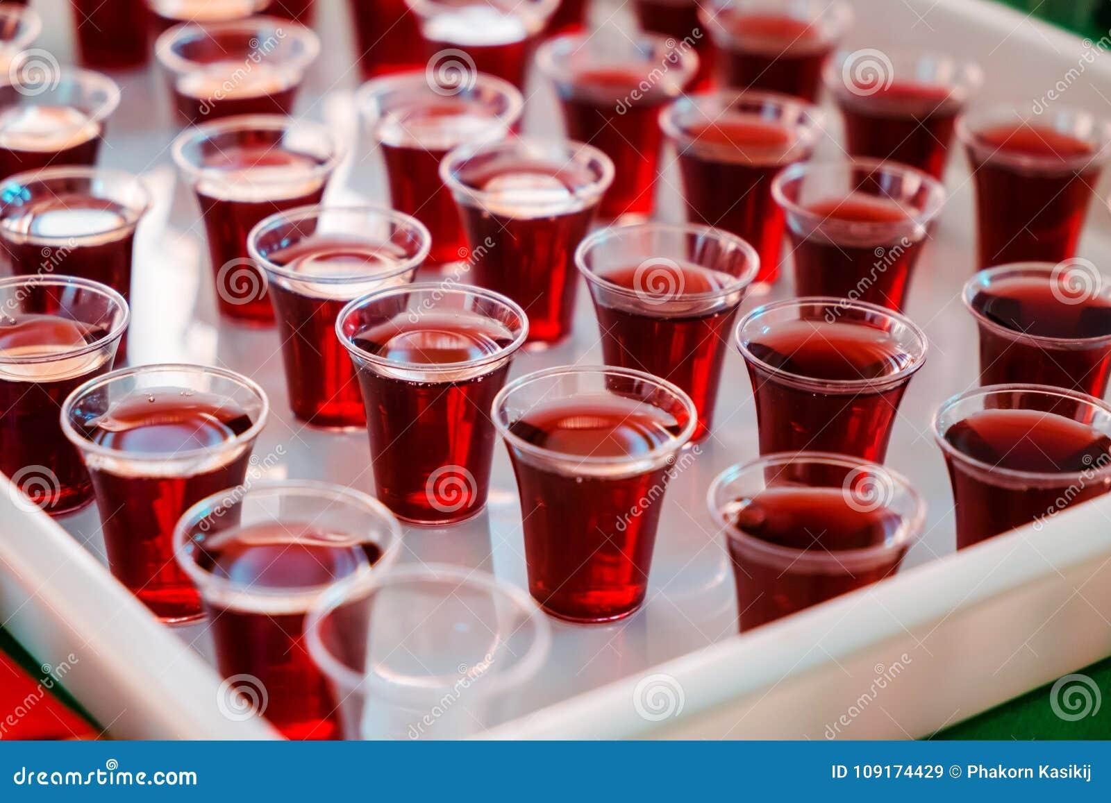 Jugo de uva en las tazas del plástico para la comunión santa en la iglesia