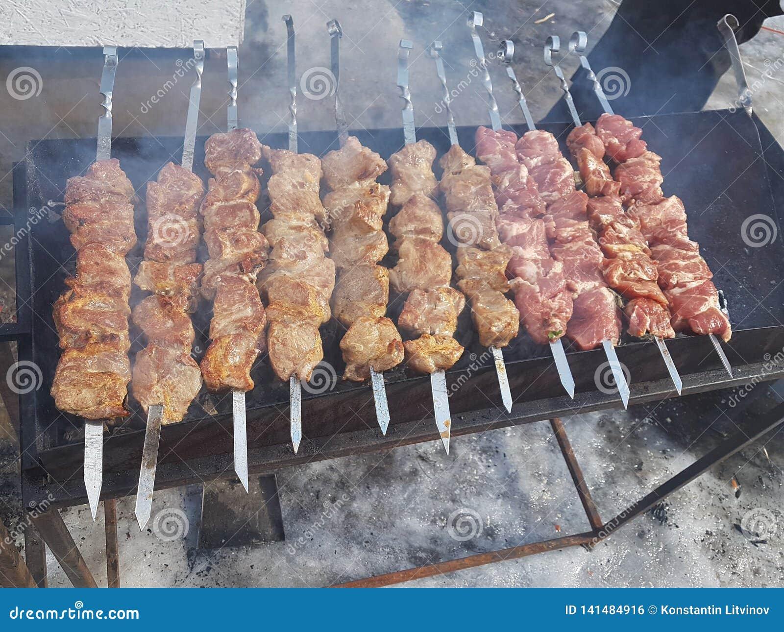 Jugoso adobado en kebab de la carne de las especias en los pinchos, cocinado y frito en una parrilla de la barbacoa del fuego y d