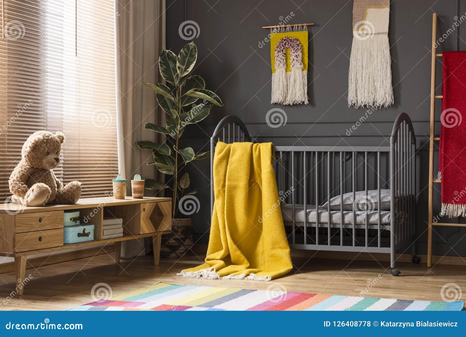Juguete de la felpa en armario de madera al lado de la cama gris con el blanke amarillo