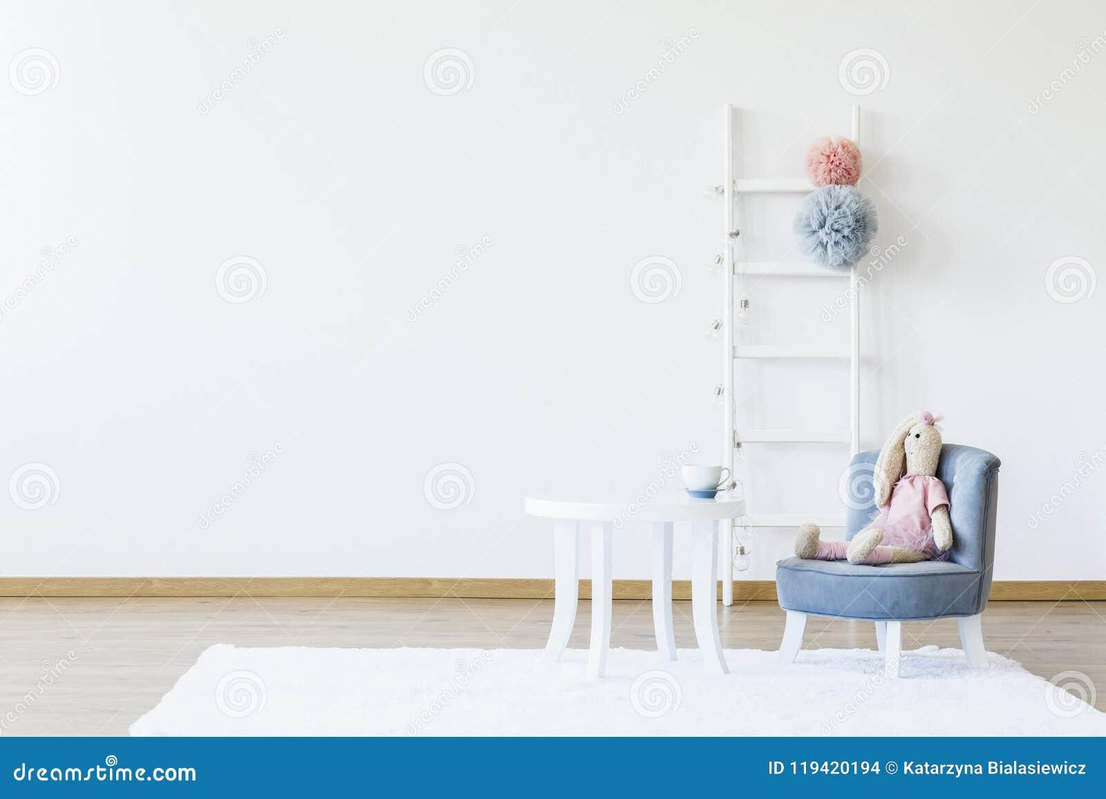 Juguete de la felpa en silla gris en la tabla blanca en el sitio mínimo i del ` s del niño
