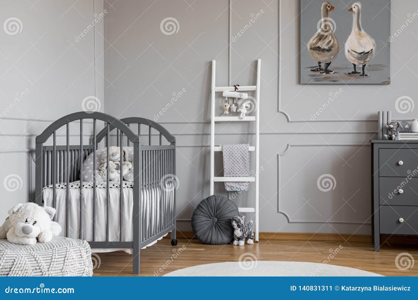 Juguete de la felpa en taburete delante de la cama gris en el interior del dormitorio del niño con la escalera y el cartel Foto v