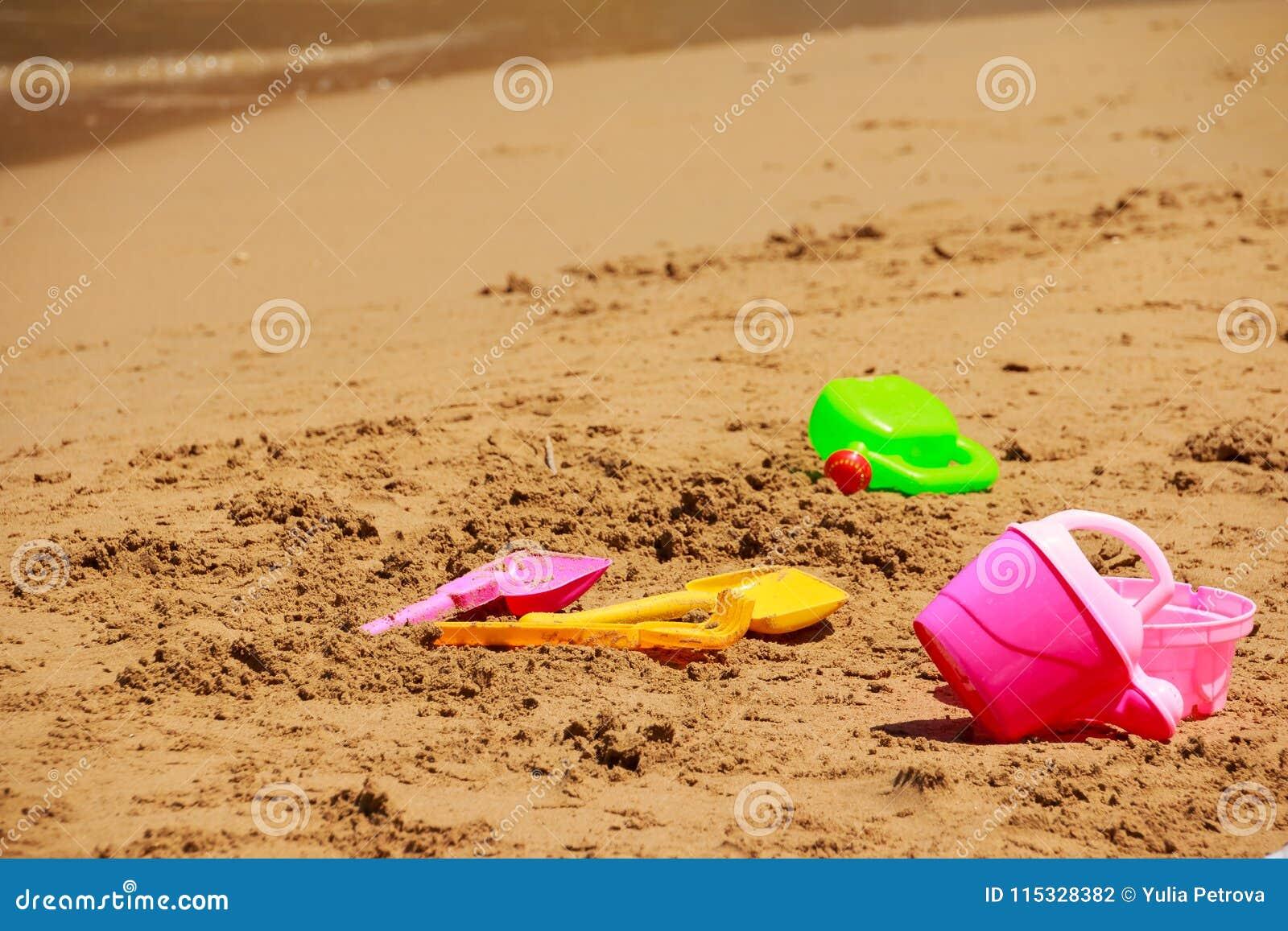 Juguetes de la playa del ` s de los niños La imagen de las vacaciones de la playa del ` s de los niños juega en la arena Sistema