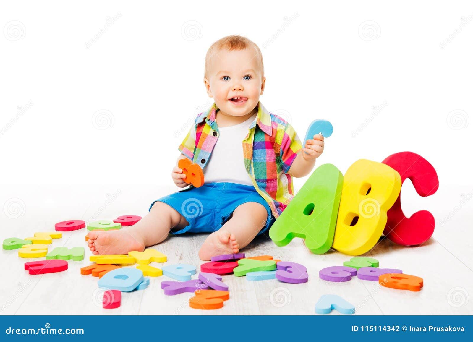 Juguetes del alfabeto del bebé, niño que juega las letras coloridas de ABC en blanco