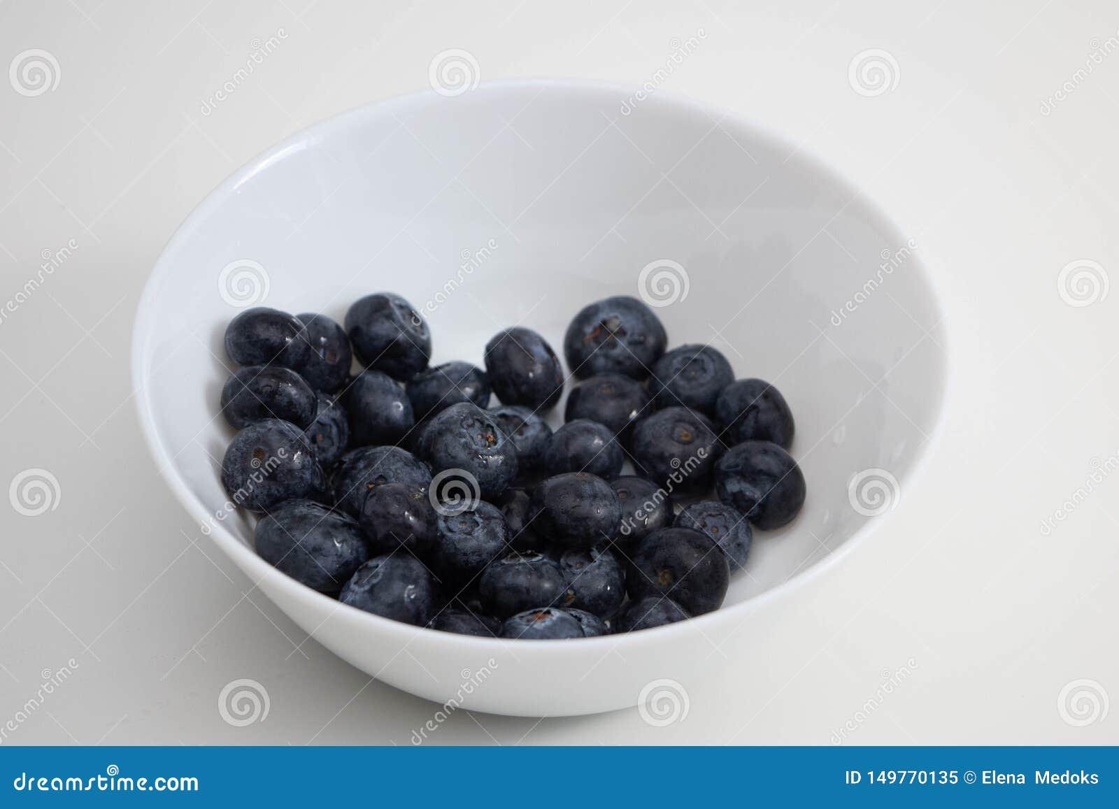 Juicy βατόμουρα σε ένα άσπρο κύπελλο, μούρα σε ένα άσπρο πιάτο σε ένα άσπρο υπόβαθρο