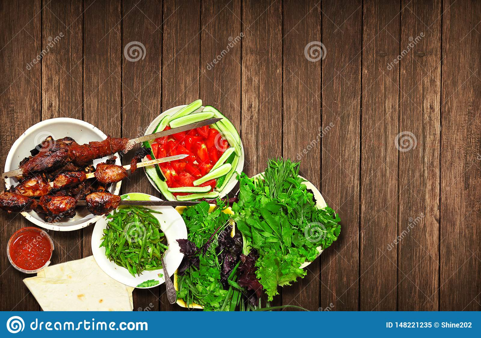 Meat kebab of lamb and beef with fresh herbs appetizing lie on a wooden table