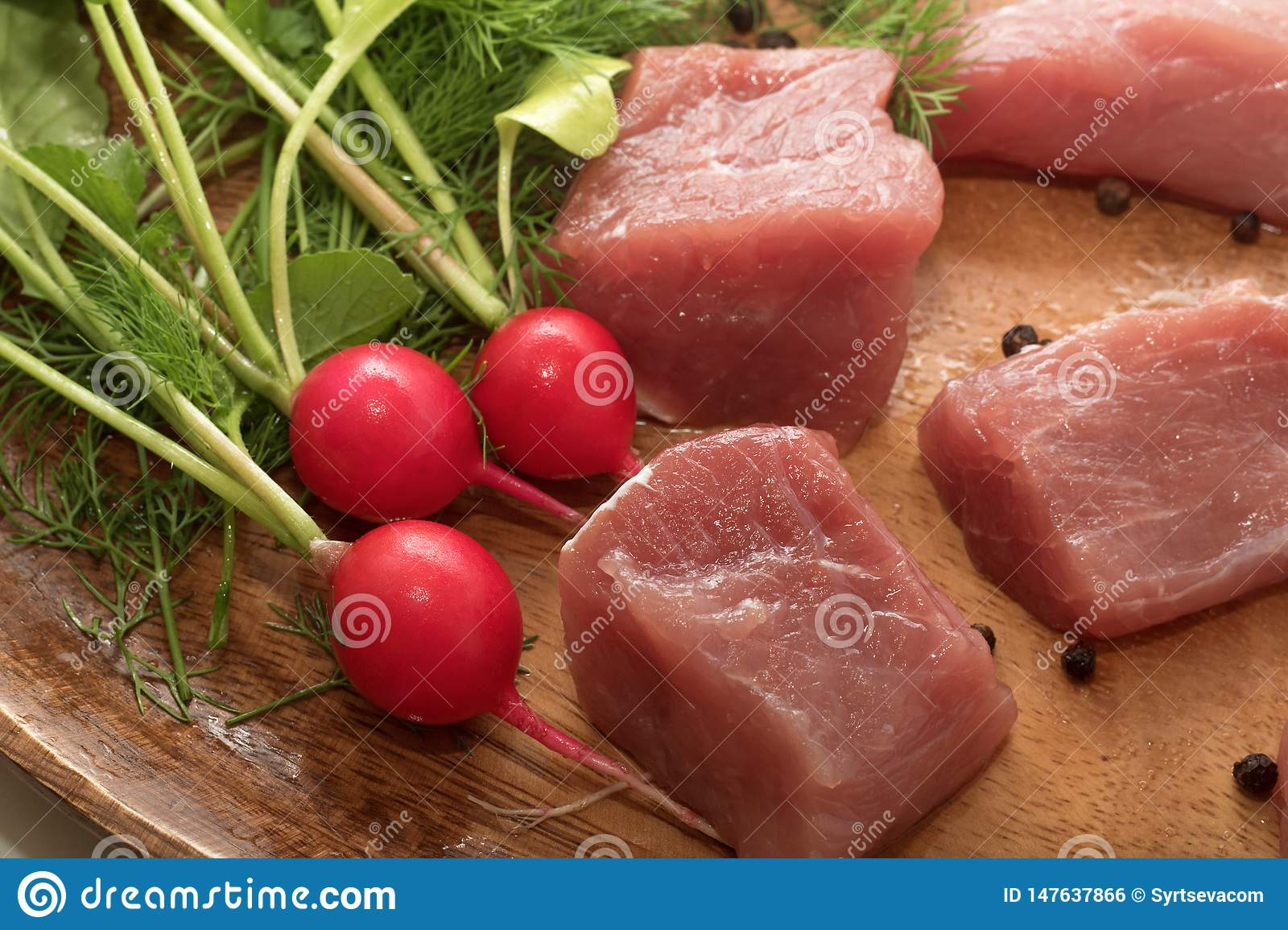 Juicy piece of meat served on a wooden plate with seasoning, herbs and vegetables