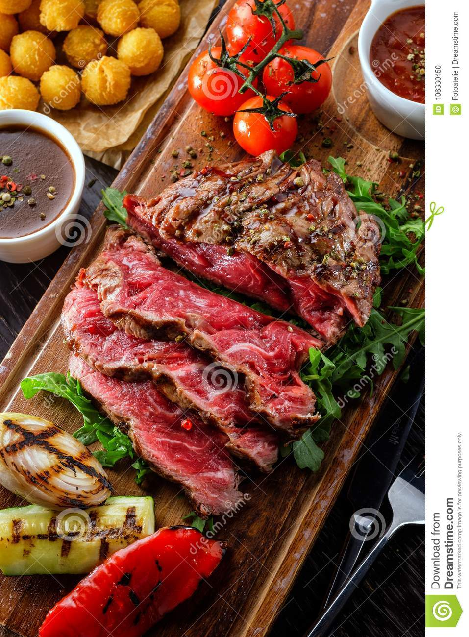 Juicy rare sliced grilled fillet steak served with tomatoes and