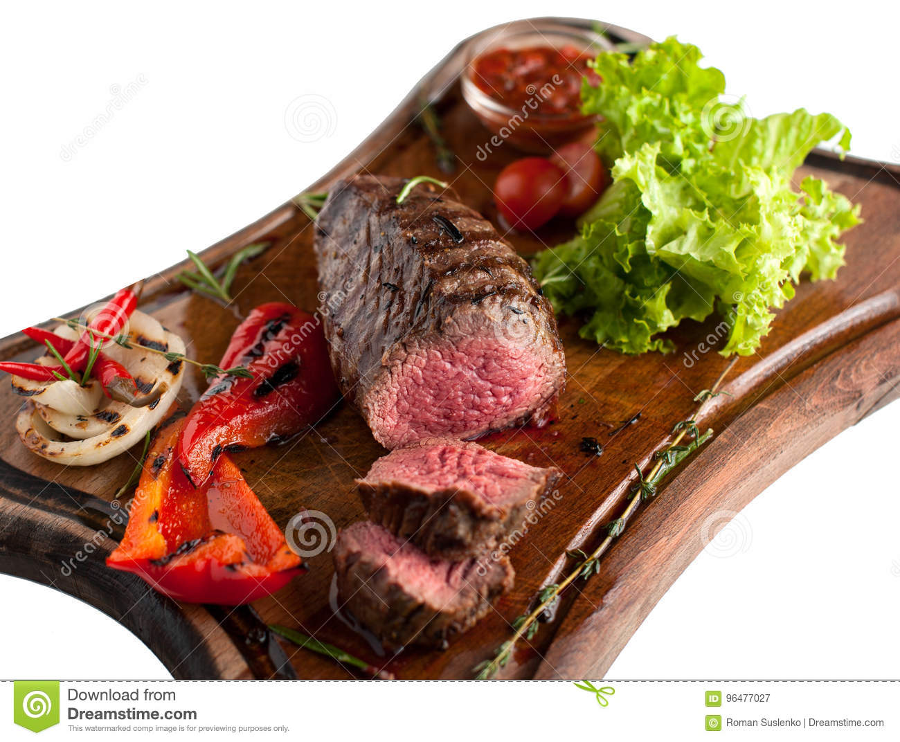 Juicy steak fillet mignon made from marbled beef with baked vegetables on a  wooden board. Sliced. Isolated abb1c23d18c9